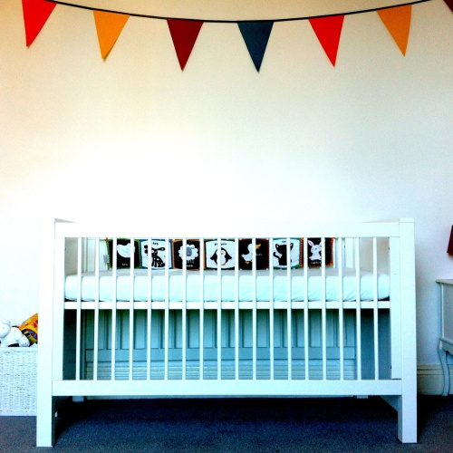 Hand me down cot from big sis, and paper bunting made by me when heavily pregnant