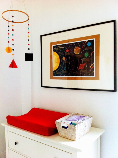 A mobile made from an embroidery hoop and thread, felt balls and craft foam (bold shapes for little eyes). Velvet changing mat cover from The Little Baby Company. And solar system poster from Ben Newman.